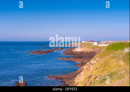 rocky seascape and houses at coast - Stock Image