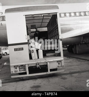 1960s, historical, Heathrow Airport, London, England, UK. Luggage truck with internal conveyor belt on the runway. - Stock Image