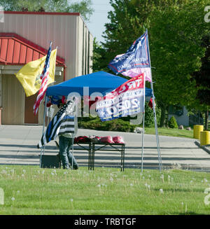 Manitowoc, Wisconsin USA, 2nd June, 2019.  Donald Trump 2020 reelection campaign getting off to an early start in Manitowoc.  Street vendor displays various American flags and Keep America Great Hats as well as campaign literature.   Credit: Jerome Wilson/Alamy - Stock Image