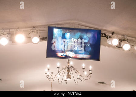 TV monitor celebrating the life and sacrifice of Jesus Christ during a Church Communion service. - Stock Image