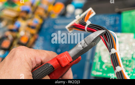 Connector, cables and hand with pliers. E-waste disposal close-up. Work of technical specialist. Colorful heap of old discarded laptop and PC parts. - Stock Image