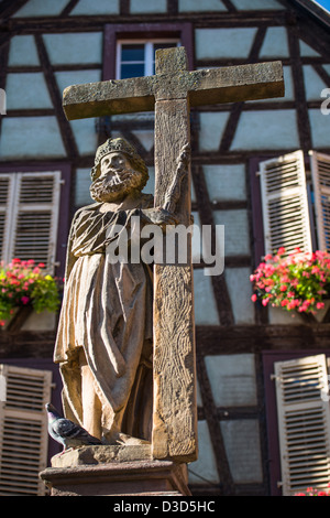 Statue at the top of the fountain in front of the Sainte Croix church, Kaysersberg, France - Stock Image
