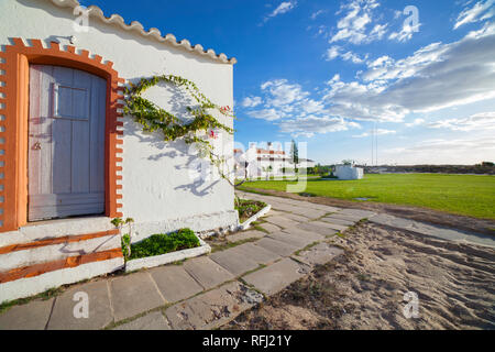 Former whitewashed fishermen huts, converted into tourist facilities at Praia do Barril beach, Tavira, Algarve, Portugal - Stock Image