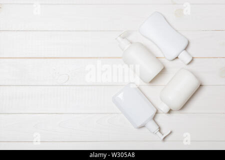 Set of White Cosmetic containers on wooden background, top view with copy space. Group of plastic bodycare bottle containers with empty space for you - Stock Image