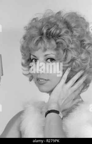 young blonde female wearing a boa  checking her blonde hair using a hand mirror 1970s hungary - Stock Image