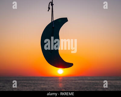 Sunrise in Thassos with the sun, the sea and a model moon. Focus on the model moon - Stock Image