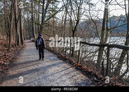 Krumme Lanke Lake, Berlin, Germany.Senior elderly man with rucksack walking along woodland path next to fozen lake - Stock Image