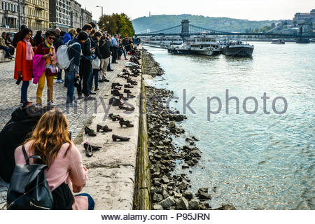Tourists visit and take photos at The Shoes on the Danube Bank, a memorial in Budapest, Hungary with the Chain Bridge and boats in the background - Stock Image