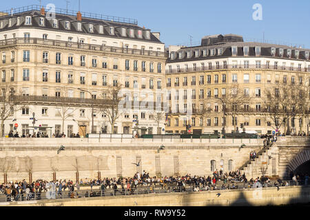People relaxing on the right embankment of the Seine River on a spring day in Paris, France. - Stock Image