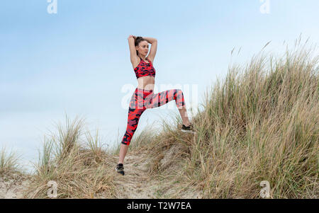 woman doing warm up stretching exercises outside in the sand dunes, wearing colourful sportswear - Stock Image