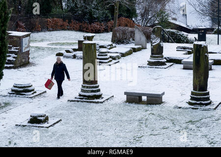 Chester, Cheshire, UK. 30th December 2018. A woman walks through the snow covered Roman Gardens in the city centre. Credit: Andrew Paterson/Alamy Live News - Stock Image