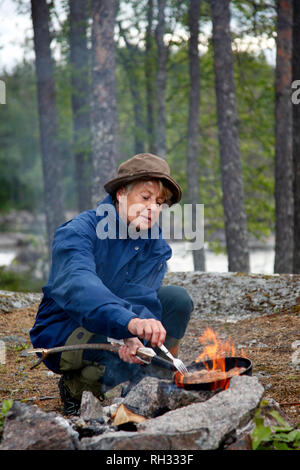 Woman cooking over fire - Stock Image