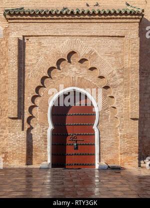 Door to Koutoubia Mosque reflected in wet sidewalk, Marrakesh, Morocco - Stock Image