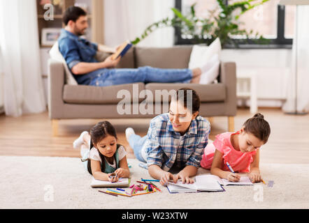 mother with little daughters drawing at home - Stock Image