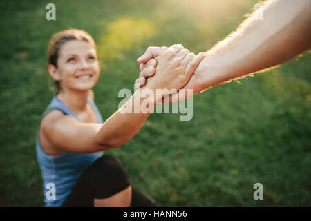 Close up shot of man helping woman to stand up. Focus on hands of couple exercising at park. - Stock Image