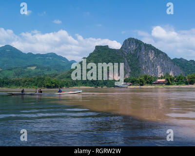 Wooden canoe on mighty Mekong River near Pak Ou Laos Asia with scenic view of jungle covered mountains - Stock Image