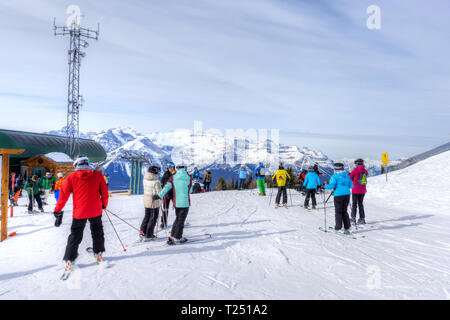 LAKE LOUISE, CANADA - MAR 23, 2019: Skiers at top of the Canadian Rockies at Lake Louise with Mount Victoria in the background. The area is popular wi - Stock Image