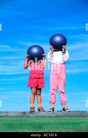 5 & 8 year old sisters holding  blue spheres in front of their faces - Stock Image