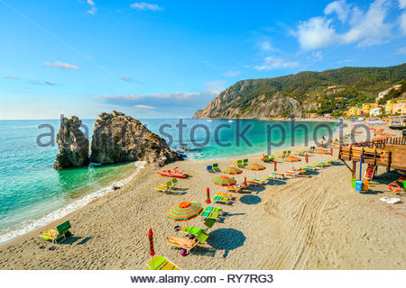 Tourists relax in the Ligurian Sea by the large rock on the Spiaggia di Fegina, the sandy beach at Monterosso al Mare, Italy, Cinque Terre - Stock Image
