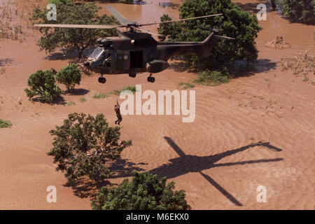 Floods in Mozambique, March 2000; A South African Air Force helicopter rescues stranded people from rooftops near - Stock Image
