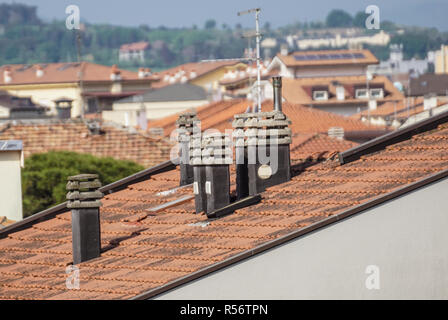 Old clay chimney pots and brick chimney stacks on old tiled roof complete with TV aerials in England, - Stock Image