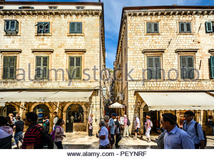 Dubrovnik, Croatia - October 1 2017: Tourists walk the main street or Stradun as they pass a narrow staircase up to the wall in Dubrovnik Croatia - Stock Image