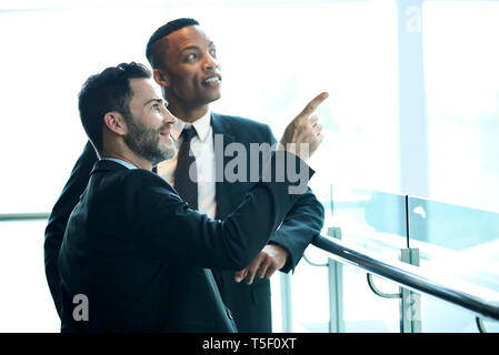 Businessmen looking outside the hotel window - Stock Image