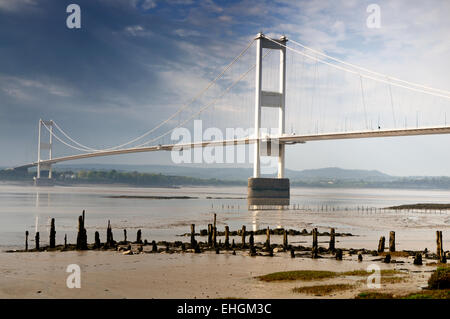 The first Severn suspension bridge spanning the Severn estuary juxtaposed with the remains of a jetty  and older - Stock Image