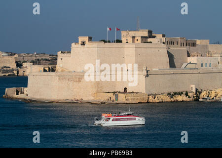 The Malta Grand Harbour ferry passing by historic Fort St Angelo while crossing from Valletta to Birgu. Travel and tourism in Malta. - Stock Image