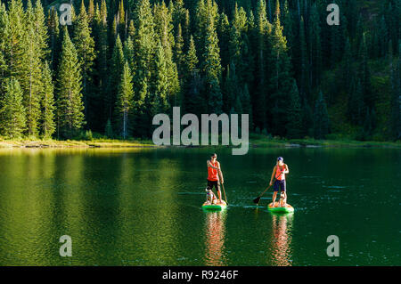View of an adventurous couple paddle boarding on a lake, Crested Butte, Colorado, USA - Stock Image