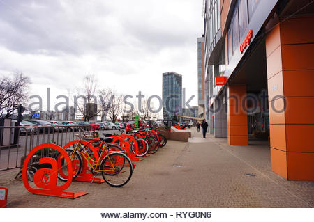 Poznan, Poland - March 8, 2019: Bicycles locked on racks in front of a Orange shop in the Globis office building on the Roosevelta street. - Stock Image