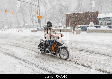 Driving motorcycle in heavy snow storm in winter, Fifth ave., Manhattan, New York - Stock Image