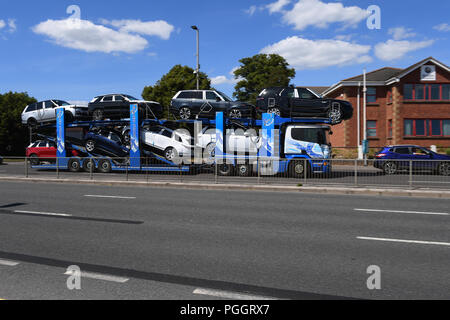 A car transporter drives along a dual carriageway fully laden with Range Rover cars on way to Southampton docks for export. - Stock Image