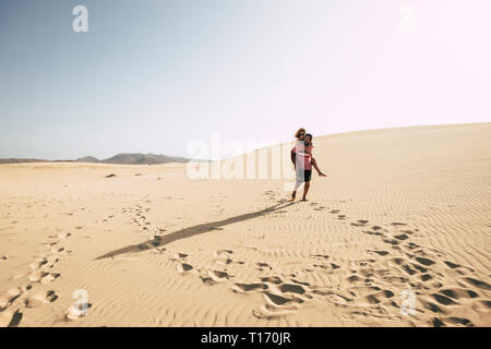 Happy traveler couple enjoy the desert dunes carrying eachother with love and fun - Caucasian people tourists walk together on the beach in outdoor le - Stock Image