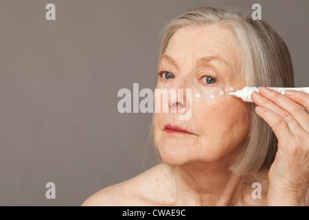 Senior woman applying eye cream - Stock Image