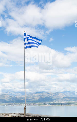 National symbol of Greece, blue-white greek flag on flagpole, sea water and blue sky, copy space - Stock Image