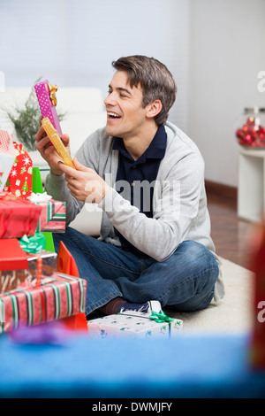 Smiling Man Holding Christmas Presents At Home - Stock Image