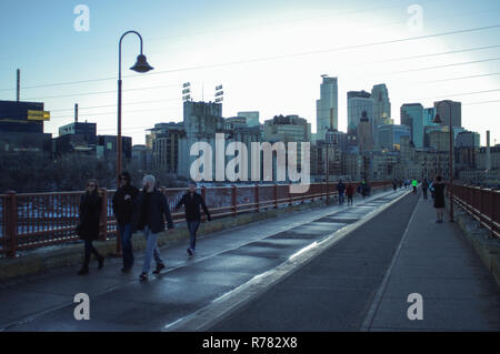View of Minneapolis skyline across Stone Arch bridge with people in foreground - Stock Image
