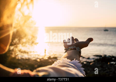 Sunset sunlight folden colors and ocean in background- woman with accessories with and to take the quiet sea - vacation and travel concept for wanderl - Stock Image