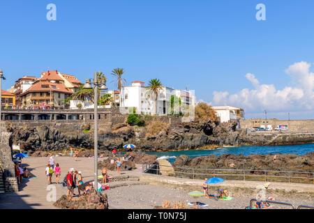 Holiday makers swimming near the harbour, Puerto De La Cruz, Tenerife - Stock Image