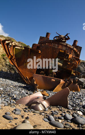 Withered, half buried in the sand beach, propeller in a low perspective at the stern of a wrecked pusher boat. Focus - Stock Image
