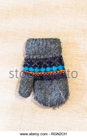 Small gray child winter glove laying on material. - Stock Image