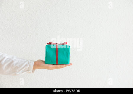 Young caucasian woman holds in hand gift box wrapped in green paper tied with red ribbon. White background. Christmas New Years Valentine Birthday pre - Stock Image
