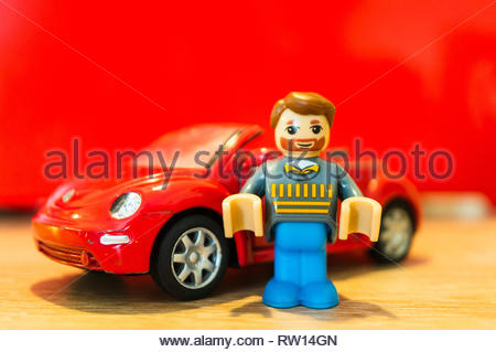 Poznan, Poland - February 15, 2019: Toy man with beard figure standing next to his parked red Volkswagen Beetle cabrio. - Stock Image
