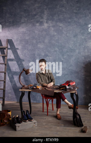 boss craftsman controlling the work of shoemakers, full length photo - Stock Image