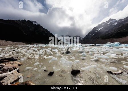 Small blocks of ice dot the shore of a glacial lake at Fitzroy in Argentina - Stock Image