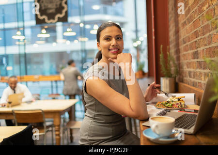 Confident businesswoman eating lunch and working in cafe - Stock Image