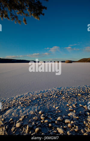 An ice covered lake in northern Sweden is illuminated by the low winter sun. - Stock Image