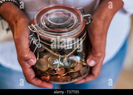 Middle age caucasian woman show her income to travel for the next vacation or adventure - european euro coin in a glass vase - home economy concept fo - Stock Image