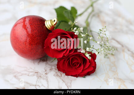 Red and white flowers with beautiful glittery Christmas ornaments. Photographed on a white marble surface. A still life photo with Christmas theme. - Stock Image
